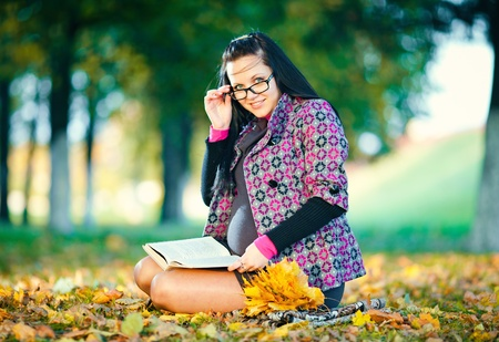 Pregnant woman in autumn park reading book