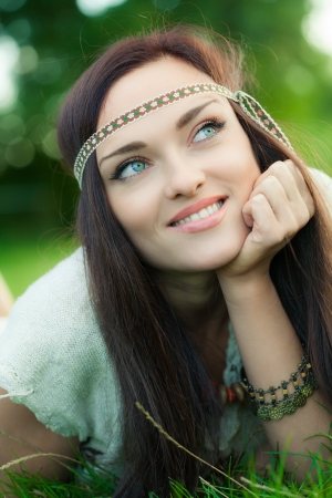 Smiling hippie girl on green grass Stock fotó