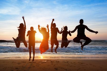 Zes mensen met een schaduw werpen op hen springen op het strand bij zonsondergang. Stockfoto