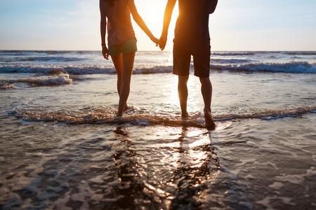 로맨스: 일몰 해변에 산책하는 젊은 부부