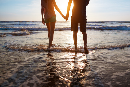 holding back: Young couple walking on the beach at sunset Stock Photo