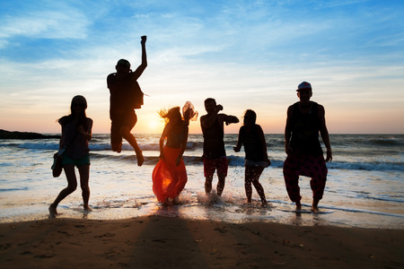 six people: Six people with a shadow cast on them are jumping on beach at sunset.