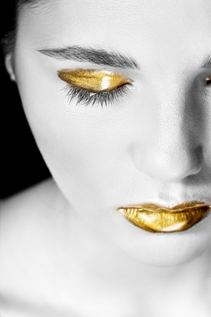 bronzed: Woman with gold make-up and shiny lips. Black and wihte.