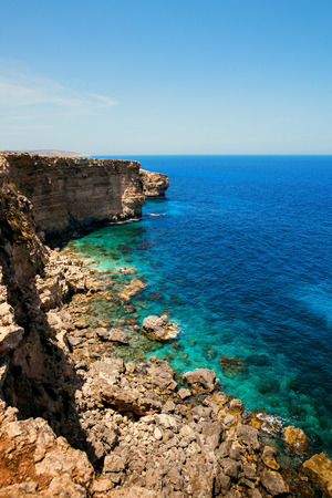 textured wall: Rocks with caves and clear turquoise water of popular tourist attraction on Malta Stock Photo