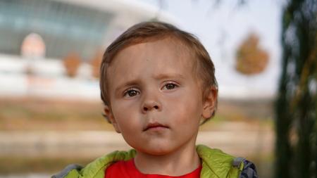 Cute serious boy portrait outdoors in the park near staduim Standard-Bild