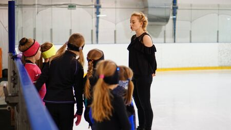 Female coach in figure skating talk to little pupils s at indoor rink