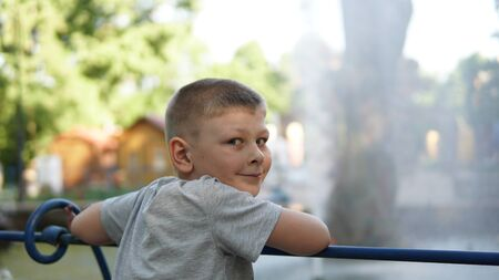 Close up portrait of caucasian teen boy. Funny cute teenager in summer park at day near the fountain. Child looking at camera. Standard-Bild