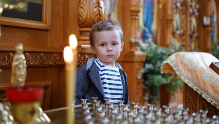 Little boy look at the candle in Orthodox Church, first visit and first impression in a Church