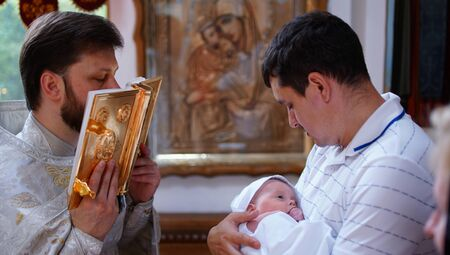 The sacrament of baptism. Orthodoxal Christening the baby. Child, priest and godfather.
