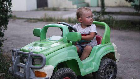 Mały chłopiec w wieku przedszkolnym jazdy duży zielony samochód zabawka i zabawy, na zewnątrz. Aktywny wypoczynek z dziećmi w ciepły letni dzień.