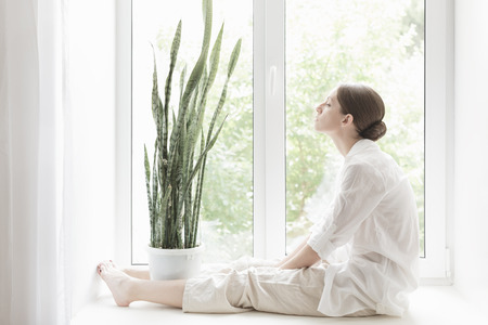 home decorations: Woman sitting on a windowsill Stock Photo