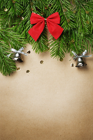 silver bells: Christmas tree branches with new year toys and silver bells on brown paper background
