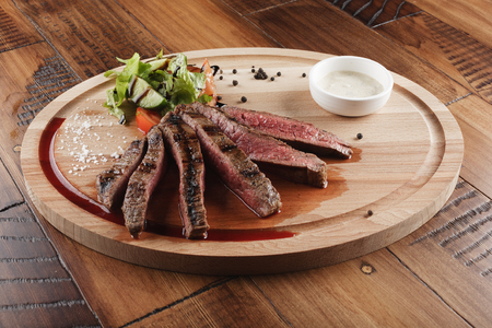 flank: Flank steak with salad and sauce on wooden surface