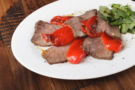 Baked roast beef with rucola and bell pepper in a white oval plate.