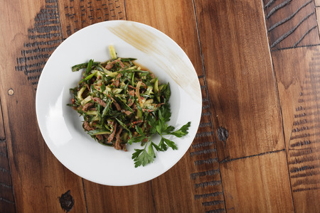wooden surface: Lazzat - uzbek traditional salad with veal meat and vegetables. Stock Photo