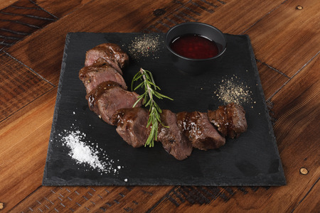 venison: Grilled venison slices with rosemary and sauce.