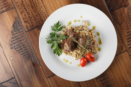 the cheeks: Veal (beef) cheeks with pearl barley porridge and greens in a white plate.