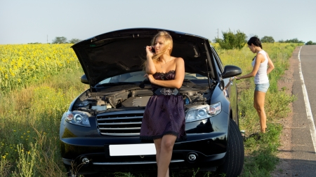journey problems: Woman phoning for help at a roadside breakdown as she sits on ther grille of the car with the bonnet raised Stock Photo