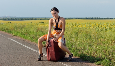 Sexy woman in stilettos sitting on a large suitcase at the roadside in the country hitching a ride photo