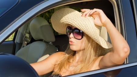 Conductor mujer hermosa en el sombrero de paja sentado en el sol caliente con la ventana del coche rod� por