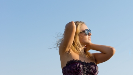 Low angle view of a beautiful woman wearing sunglasses with her head raised to the sky enjoying the sun Stock Photo - 14747241