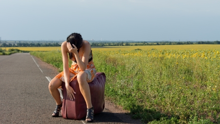 Abatido autoestopista mujer en tacones de aguja y un vestido se sienta en una maleta grande al lado de una carretera nacional con la cabeza entre las manos