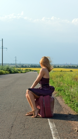 Fashionable woman in a sundress and stilettoes facing away from the camera hitchhiking at the roadside in the countryside photo