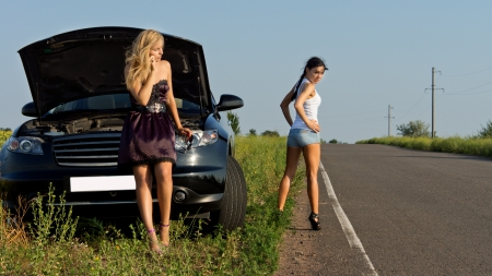 roadside assistance: Two girls wait for the help on the road