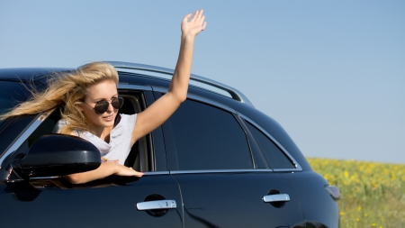 Attractive blonde woman leaning from car window waving a greeting photo
