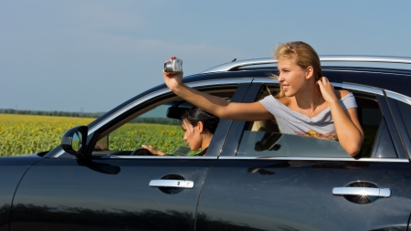 Beautiful young blonde woman passenger leaning out of car window taking a photograph of herself photo