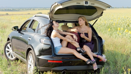 Two women relaxing in the shade of the raised boot of their station wagon as they take a break on a long journey through the countryside