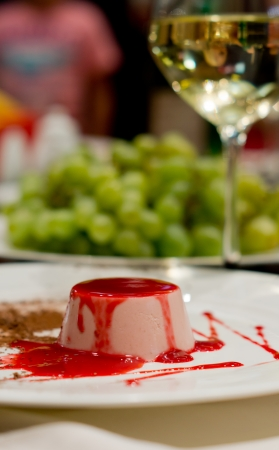 Delicious mousse dessert drizzled with a rich red fruity topping served on a table with a glass of white wine, vertical with copyspace photo