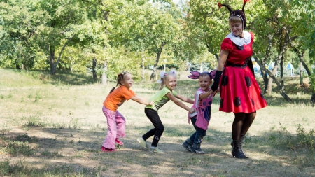 Three young children playing follow the leader led by mother outdoors in the park Фото со стока