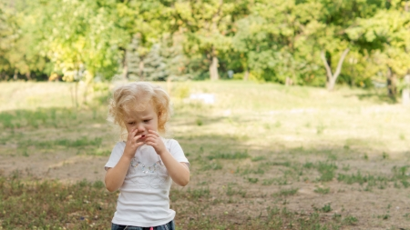 Cute shy little blonde girl in a park with her hands to her face peering shyly at the camera photo