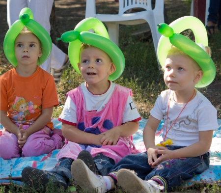 Three cute little children at a birthday party wearing hats fashioned from twisted green party balloons sitting on a rug on the grass photo
