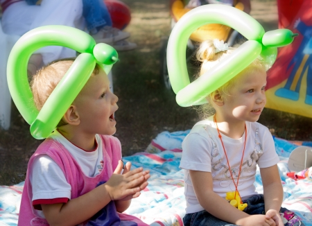 Two young blonde children wearing hats made from twisted green balloons sitting on a rug on the floor enjoying a birthday party and clapping hands Stock Photo