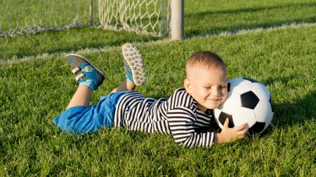 Smiling happy young boy lying on green grass at a sportsfield in evening light with a soccer ball photo