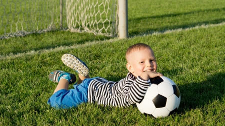 Happy little boy with his soccer ball lying on the lush green grass of a summer sportsfield in evening sunlight photo