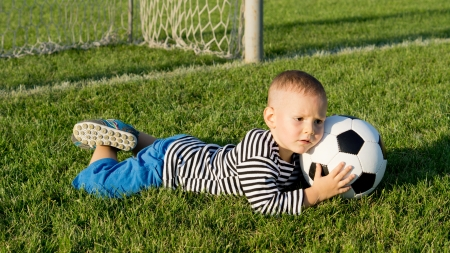 Little boy playing soccer in evening light lies on his stomach on the grass clutching the ball as he saves a goal photo