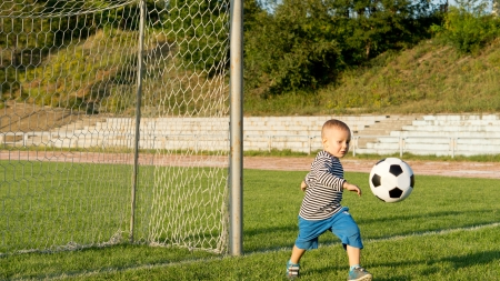 Small boy kicking a soccer ball in green grass in front of the goalposts on a sportsfield photo