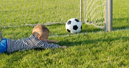 misses: Small boy lies stretched out on the green grass in the goals as he misses the soccer ball while playing goalkeeper, Stock Photo