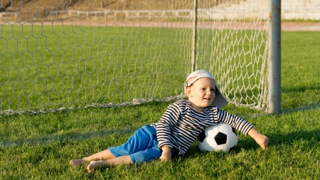 Barefoot youngster with soccer ball lying on green grass in front of goalposts on a sportsfield photo