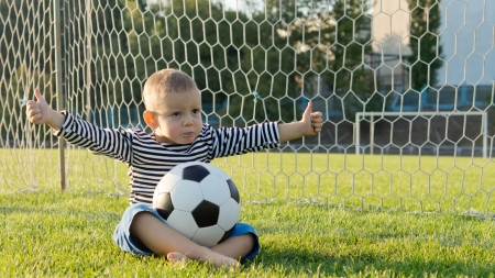 goalpost: Little sportsman sitting cross legged on green grass in the goalpost with a soccer ball on his lap giving a thumbs up Stock Photo
