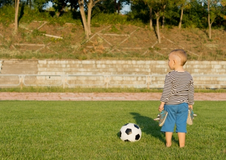 Rear view image of a small barefoot boy standing with his shoes in his hands alongside a soccer ball on green grass with copyspace photo