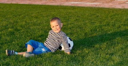Small boy lying on green grass in evening sunlight leaning back against a soccer ball photo