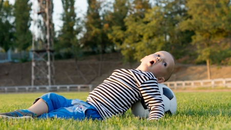liesure: Small boy lying on his back on green grass with his head resting on a soccer ball playing around