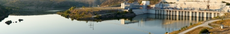 hydroelectricity: Panorama of the tranquil still waters of a dam with the wall reflected on the surface to the right and part of a lakeshore road and leisure drive just visible