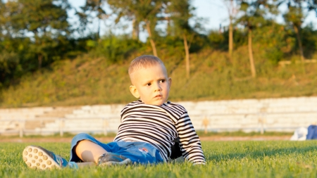 liesure: Low angle view of a cute little boy lying on his back on green grass in evening sunlight