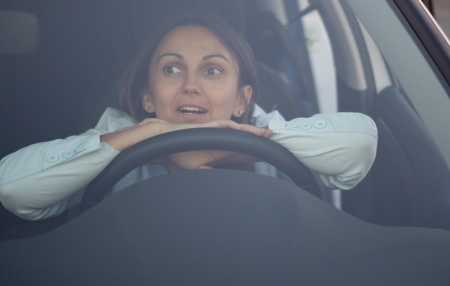 View through the windscreen of a harassed woman waiting in car with her hands and head resting on the steering wheel photo