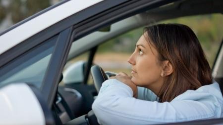 Ver a trav�s de la ventana abierta de una atractiva mujer que espera pacientemente en el coche Foto de archivo